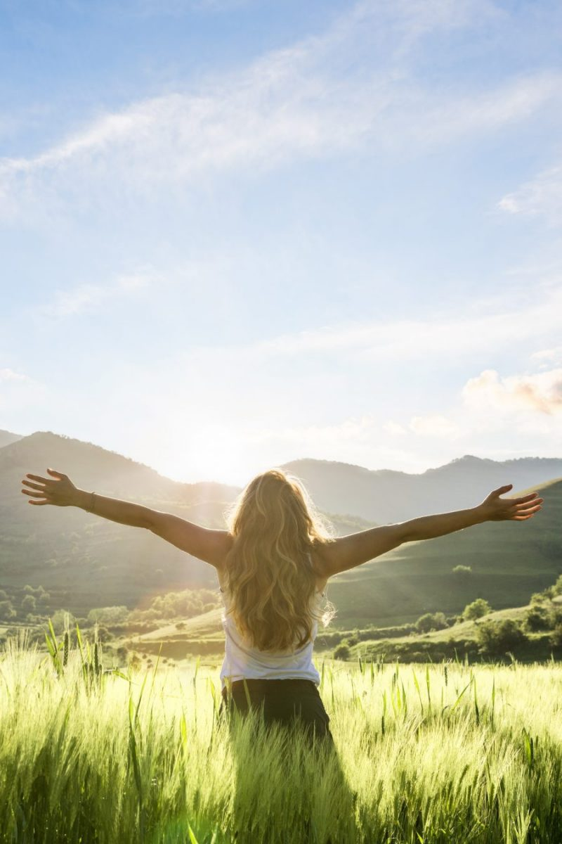 woman in nature with hands outstretched having a beautiful fresh morning